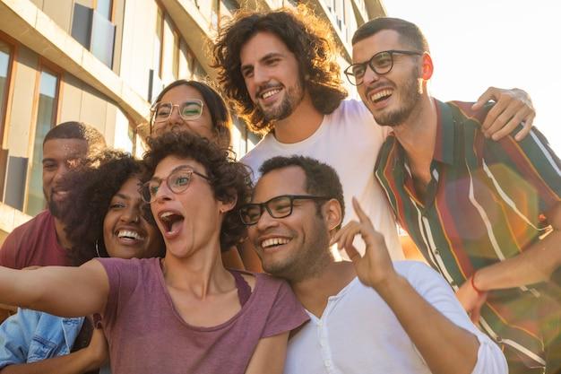 Mujer divertida de pelo rizado en gafas tomando selfie