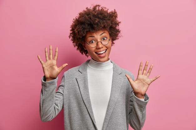 Mujer divertida con pelo rizado levanta palmas sonríe positivamente