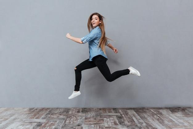 Mujer divertida saltando en estudio