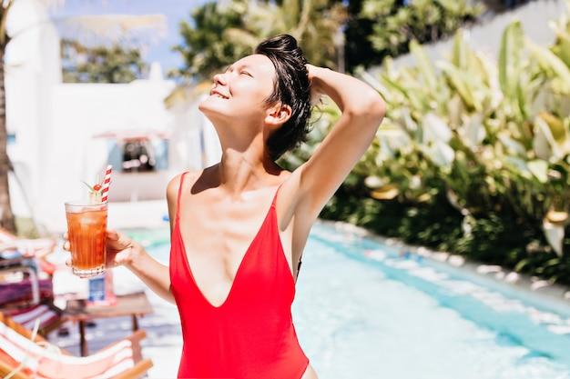 Mujer divertida en traje de baño rojo mirando hacia arriba con una sonrisa.