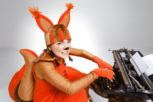 Mujer divertida vestida como una ardilla, escribiendo con una vieja máquina de escribir