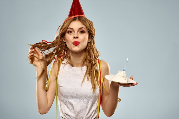 Mujer en un divertido pastel de cumpleaños de gorra de vacaciones con vela
