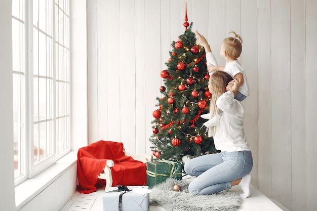La mujer se divierte preparándose para la navidad. madre con camisa blanca está jugando con su hija. la familia está descansando en una sala festiva.