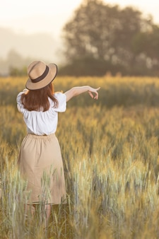 Mujer divirtiéndose en el campo de cebada en verano