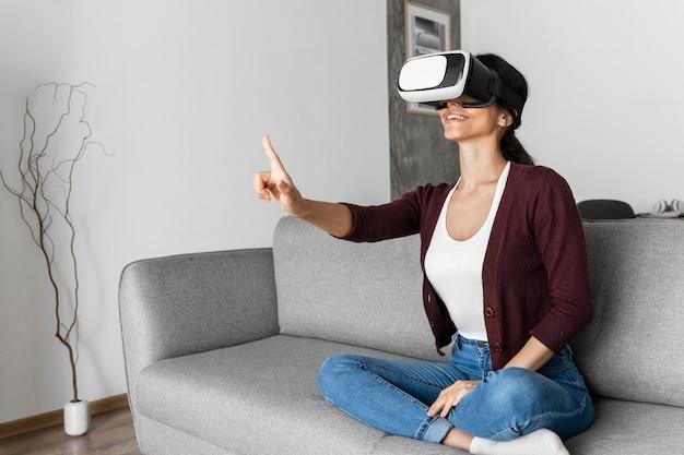Mujer divirtiéndose en casa con casco de realidad virtual