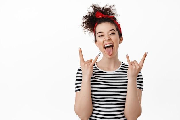 Mujer divirtiéndose, mostrando la lengua y el gesto de cuernos de heavy metal, sintiéndose libre y relajada, de pie sobre blanco