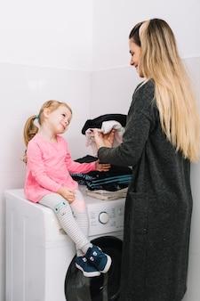Mujer doblando ropa mirando a su hija sentada en la lavadora