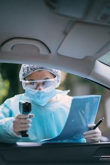 La mujer del doctor usa una pistola de termómetro infrarrojo en la frente para verificar la temperatura corporal. para los síntomas del virus covid-19. mujer con bata de aislamiento o trajes protectores y mascarillas quirúrgicas al aire libre.