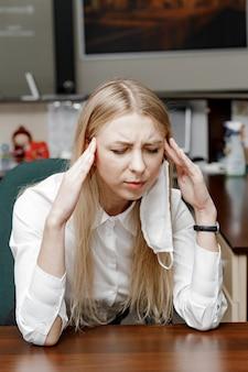 Mujer con dolor de cabeza en la oficina, sentirse enferma en el trabajo