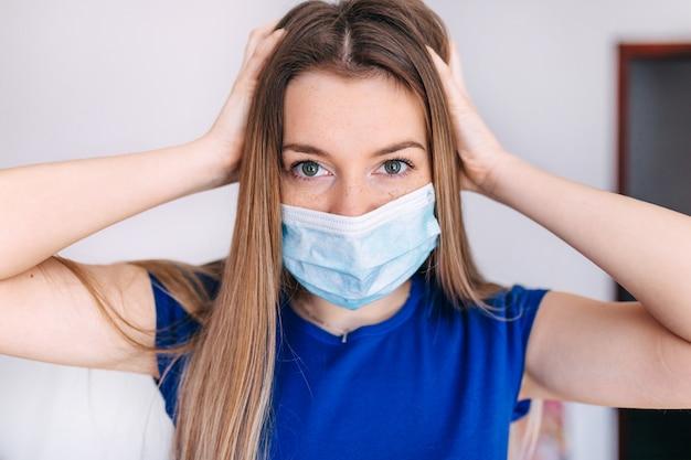 Una mujer con dolor de cabeza y síntomas de coronavirus con una máscara facial.