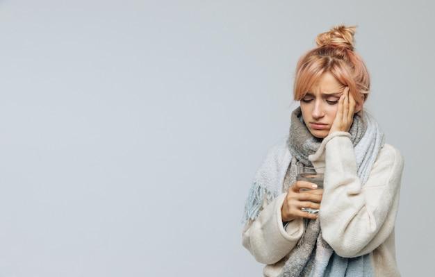 Mujer con dolor de cabeza, sosteniendo un vaso de agua, tocando su sien, sintiendo los primeros síntomas de la gripe
