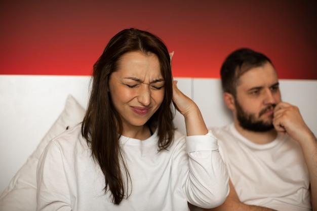 Mujer con dolor de cabeza tiene la mano en la sien, hombre cansado de problemas en la vida sexual