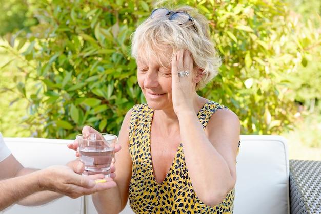 Mujer con dolor de cabeza, toma una pastilla