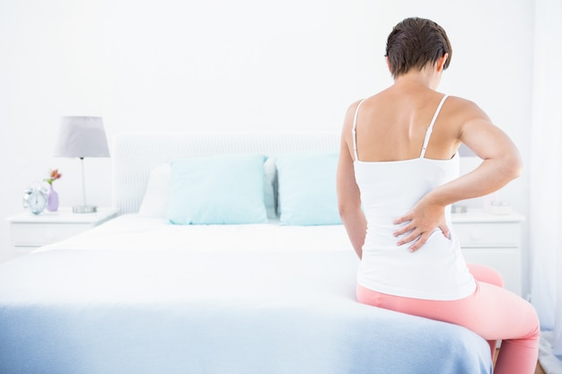 Mujer con dolor de espalda en casa en el dormitorio