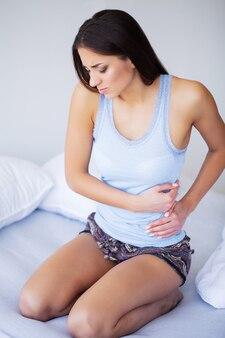 Mujer con dolor de estómago doloroso, mujer que sufre de dolor abdominal