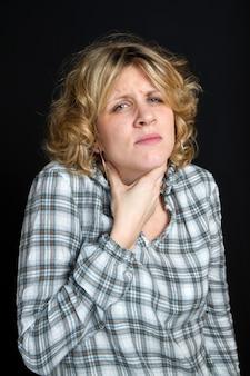 Una mujer con dolor de garganta