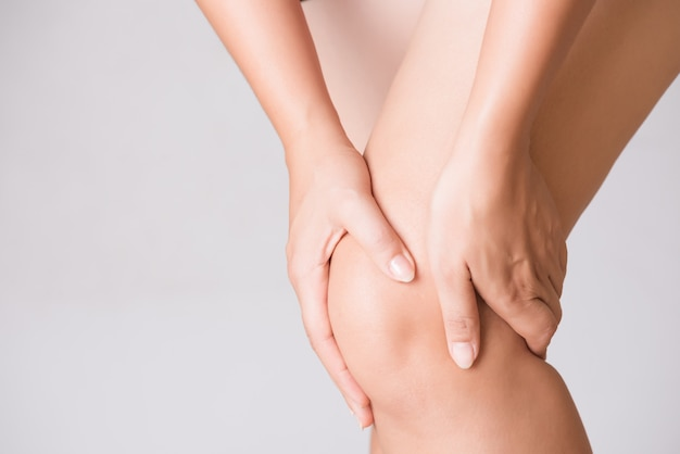 Mujer en el dolor de rodilla mientras se ejecuta. concepto de salud y médico.