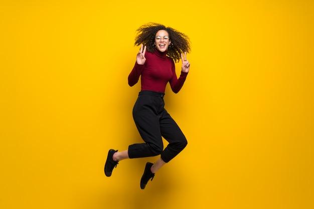 Mujer dominicana con cabello rizado saltando sobre pared amarilla