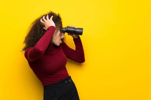 Mujer dominicana con suéter de cuello alto y mirando en la distancia con binoculares