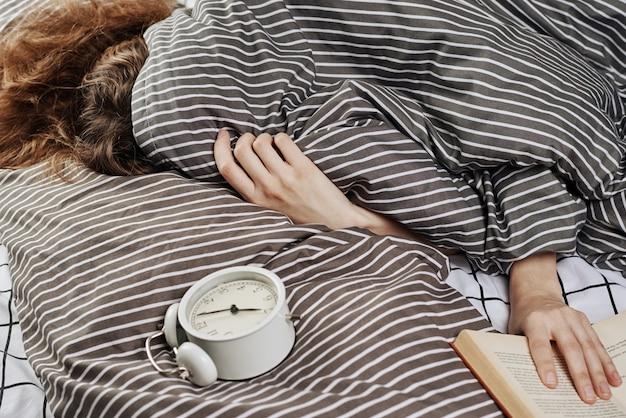 Mujer dormida cubierta bajo una manta en la cama y despertador vintage en la almohada.