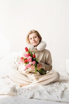 Mujer dormida sentada en la cama en pijama y almohada sobre el cuello, flores de tulipán en la cama