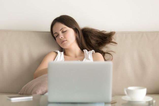 Mujer dormida en un sofá frente a una computadora portátil