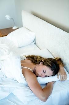 Mujer dormida en su cama, acostada sobre su estómago