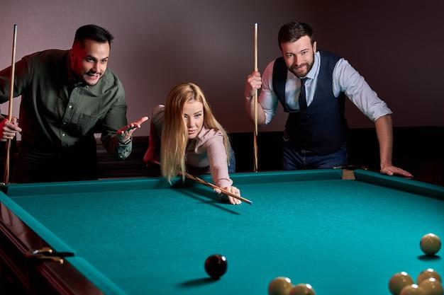 Mujer con dos amigos varones están jugando al billar en el bar después del trabajo, tienen tiempo de descanso y ocio, preparándose con el objetivo de disparar bolas de billar