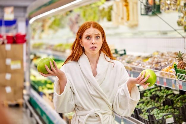 Mujer dudosa eligiendo fruta fresca, comparando, haciendo una elección a favor de lo mejor, pensando
