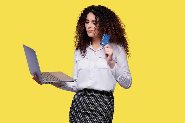 La mujer dudosa hace compras en una tienda en línea usando una computadora portátil y tiene una tarjeta bancaria en sus manos sobre fondo amarillo aislado. concepto de tienda online. compras durante la cuarentena