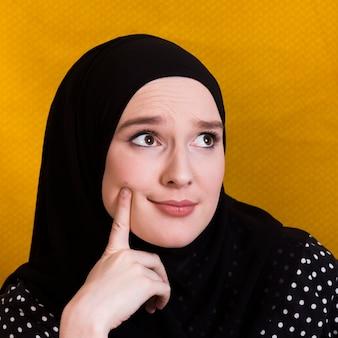Mujer dudosa pensando algo con un dedo en su mejilla