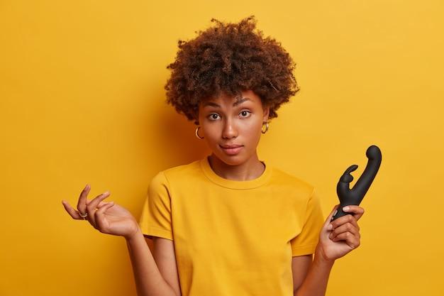 Mujer dudosa y perpleja se encoge de hombros y se siente indecisa, elige un vibrador con forma de conejo para satisfacer todas las necesidades, estimula el clítoris con vibraciones agradables, usa una camiseta amarilla, se para en el interior