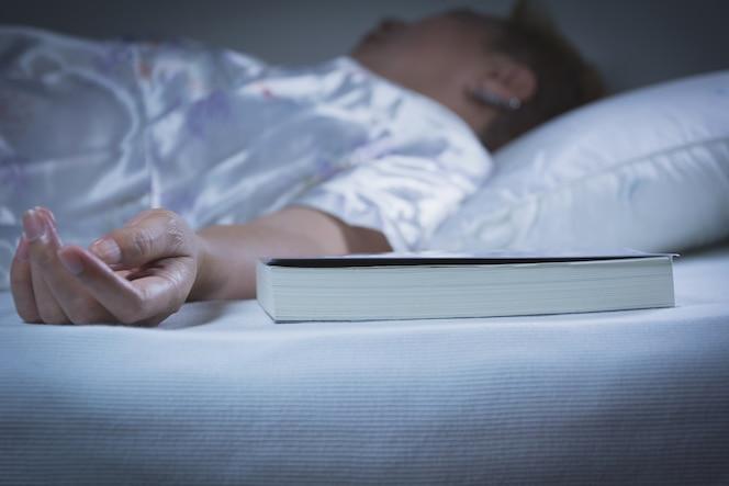 Mujer durmiendo con un libro en la cama en el dormitorio, ella está descansando con los ojos cerrados.