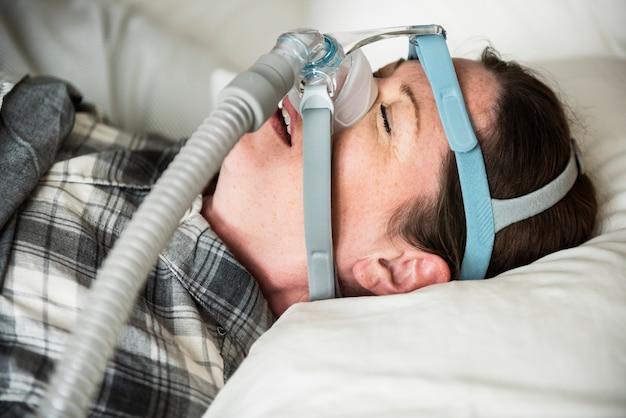 Una mujer durmiendo con correa de barbilla anti ronquidos.