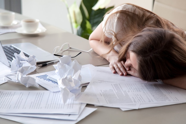 Mujer durmiendo en el escritorio cubierto de papeles arrugados