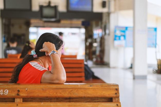 Mujer durmiendo en estaciones de autobuses con enfoque suave y luz en el fondo.