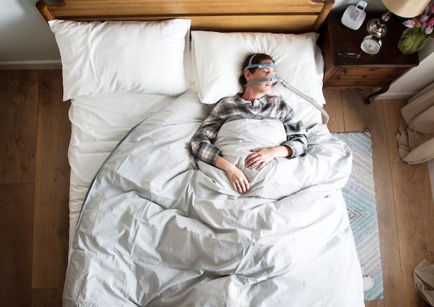 Mujer durmiendo con una máscara antirronquidos.