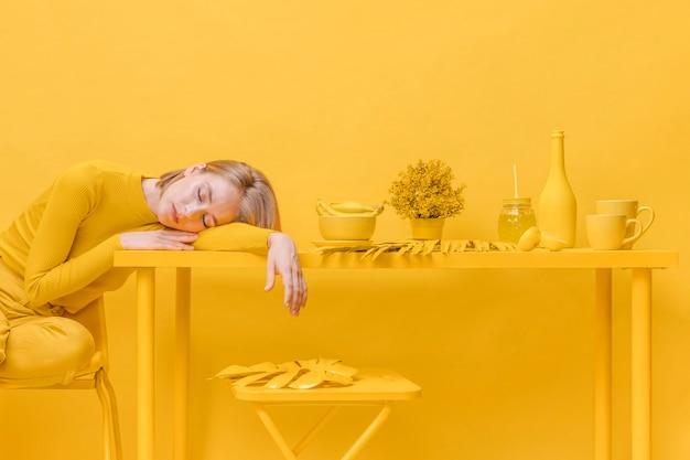 Mujer durmiendo en mesa en una escena amarilla