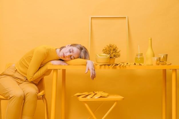 Mujer durmiendo en mesa en un escenario amarillo