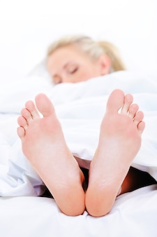 Mujer durmiendo con pies limpios que sobresalen de debajo de la colcha