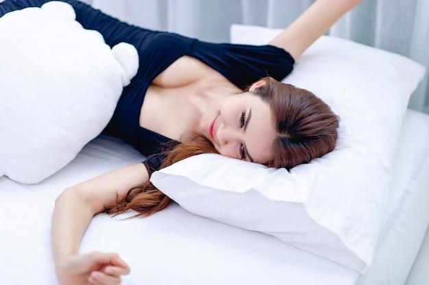 Una mujer durmiendo sobre un colchón blanco conceptos de sueño y descanso para una buena salud