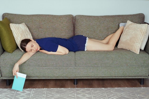 La mujer se durmió mientras leía en el sofá de la sala de estar