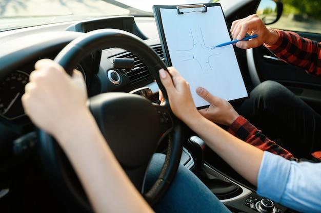 Mujer e instructor con lista de verificación en coche, autoescuela. hombre enseñando a la señora a conducir un vehículo. educación sobre licencias de conducir