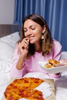Mujer east comida rápida desde la entrega en la cama en el dormitorio en casa mujer disfrutando de comida grasa pizza y hamburguesas hambrienta de carbohidratos