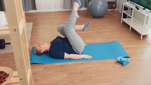 Mujer de edad avanzada ejercicio sentado en la estera de yoga en la sala de estar. entrenamiento de ejercicio de pensionista de edad avanzada en casa actividad deportiva en edad de jubilación