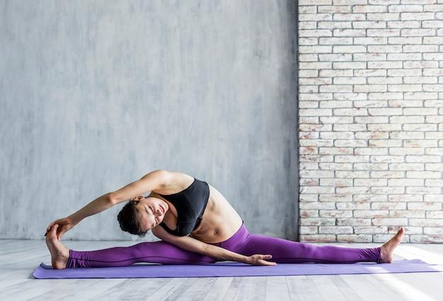 Mujer ejecutando una división lateral con el brazo extendido