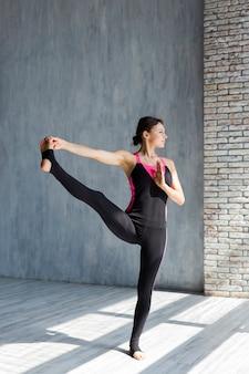 Mujer ejecutando una pose de yoga extendida de la mano al dedo gordo