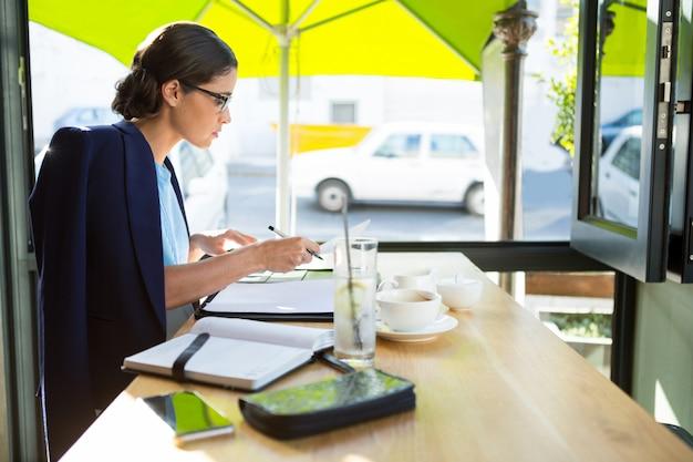 Mujer ejecutiva escribiendo en diario en el café