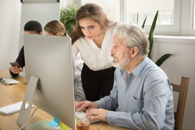 Mujer ejecutiva que enseña al oficinista mayor que ayuda a explicar el trabajo del ordenador