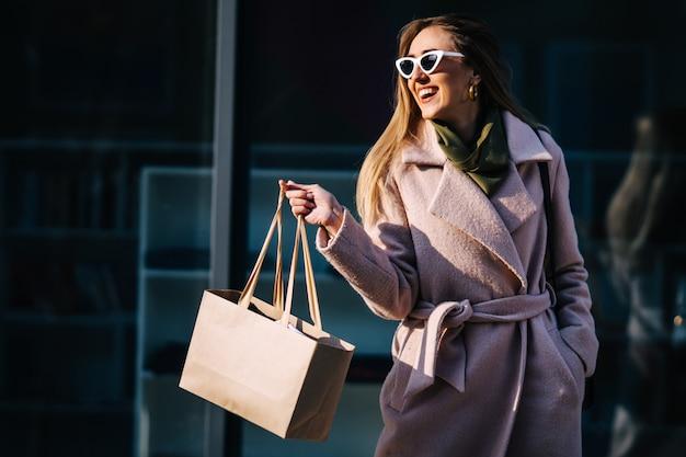 Una mujer elegante con un abrigo y gafas de sol en sus compras